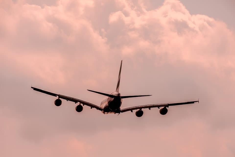 Ett passagerarflygplan som lyft mot en röd molnig himmel