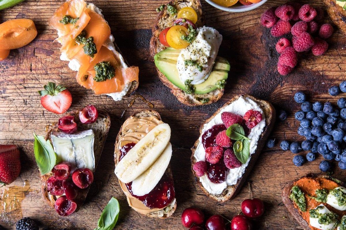 En skärbräda i trä med mackor av surdegsbröd och olika pålägg dekorerad med färska bär och frukter.