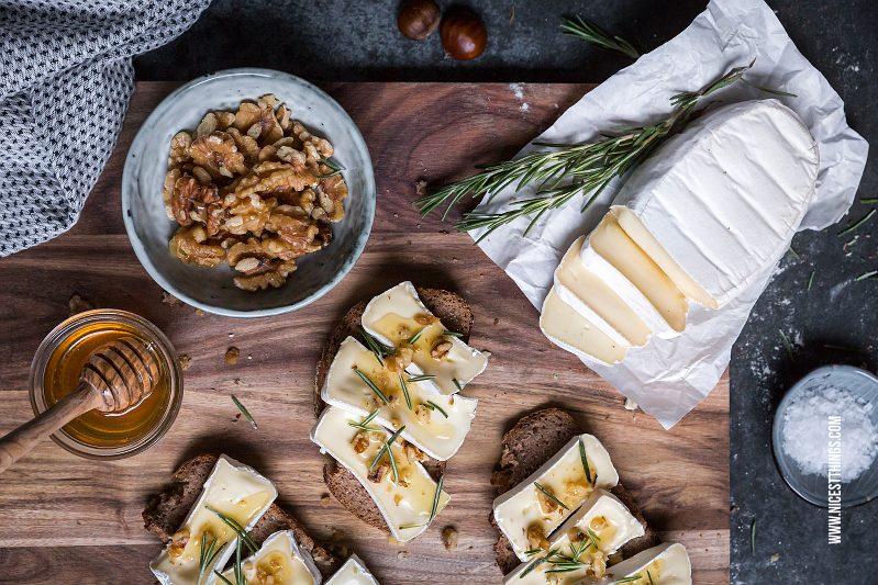 En skärbräda mot en granitbakgrund fylld med godsaker som brieost, en skål med valnötter, honung och mackor.