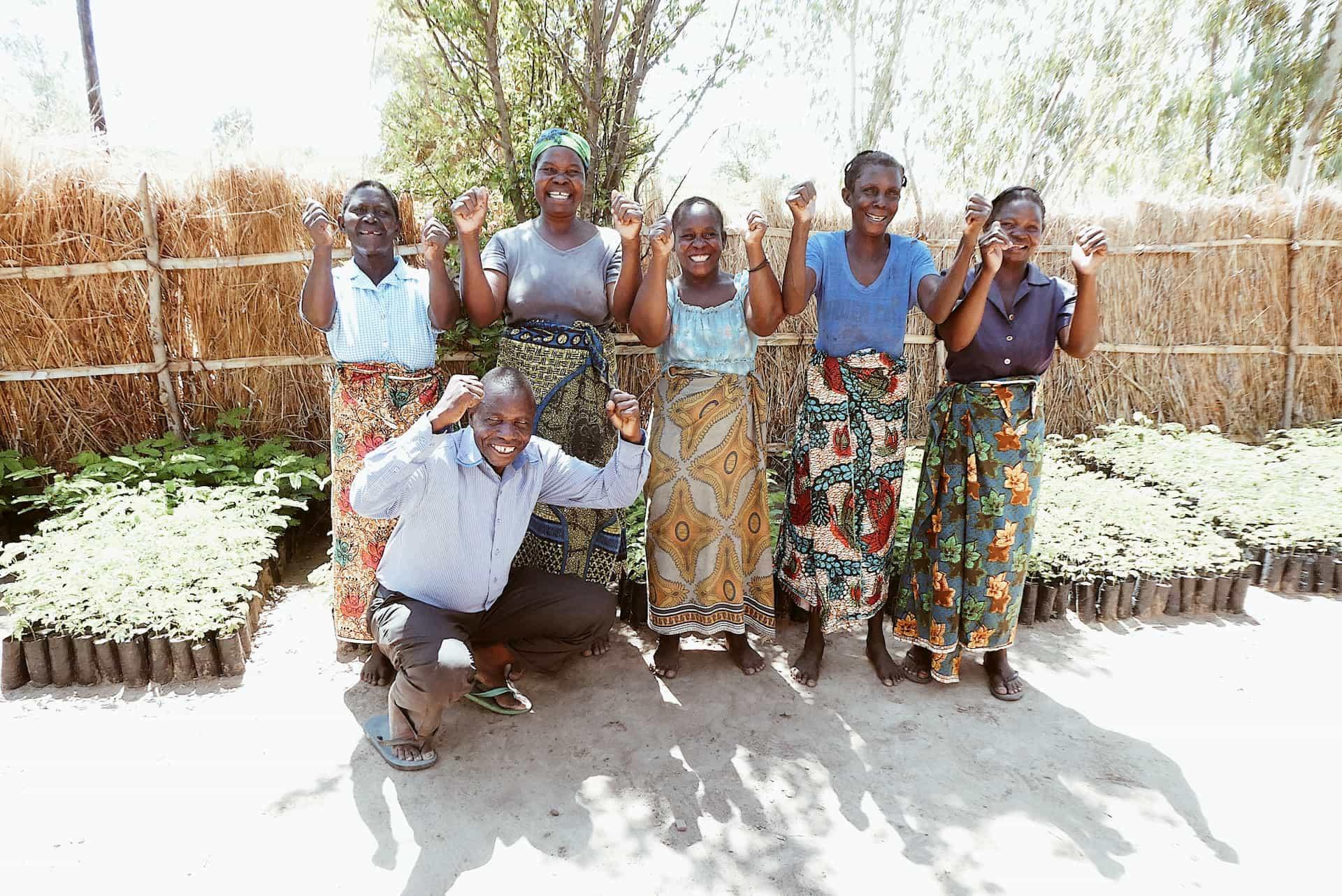 sex stycken ripple arbetare står framför krukor med växter och håller håller upp händerna i en segerviss gest.